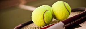 A shot of a tennis racquet and tennis balls on the tennis court